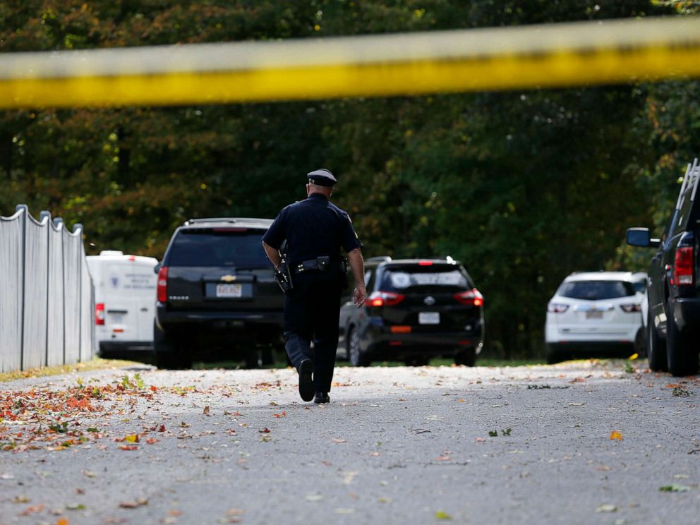 PHOTO: An officer walks towards Medical Examiners office vans as they enter the scene where three children and two adults were found deceased in their home in Abington, Mass. on Oct. 7, 2019.