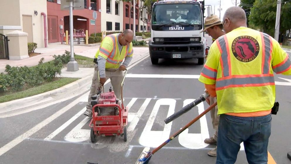 PHOTO: Workers work to fix a misspelled school crosswalk found in Doral, Fla.
