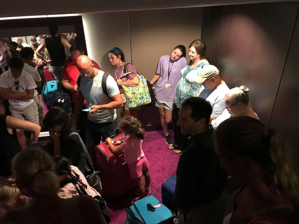 Passengers mill about the Norwegian Getaway while delayed during the search for a crew member who fell overboard on Saturday, June 30, 2018.