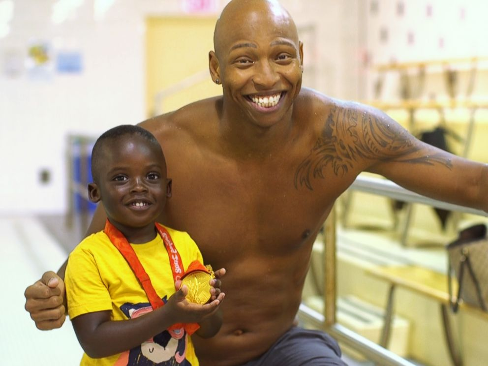 PHOTO: Olympic swimmer Cullen Jones poses with a young child after a swim class in New York.