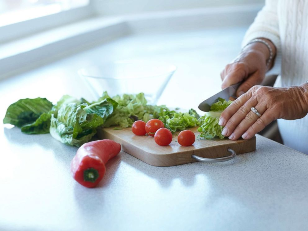 PHOTO: In this undated stock photo, a woman cuts up romaine lettuce on a cutting board for a salad.