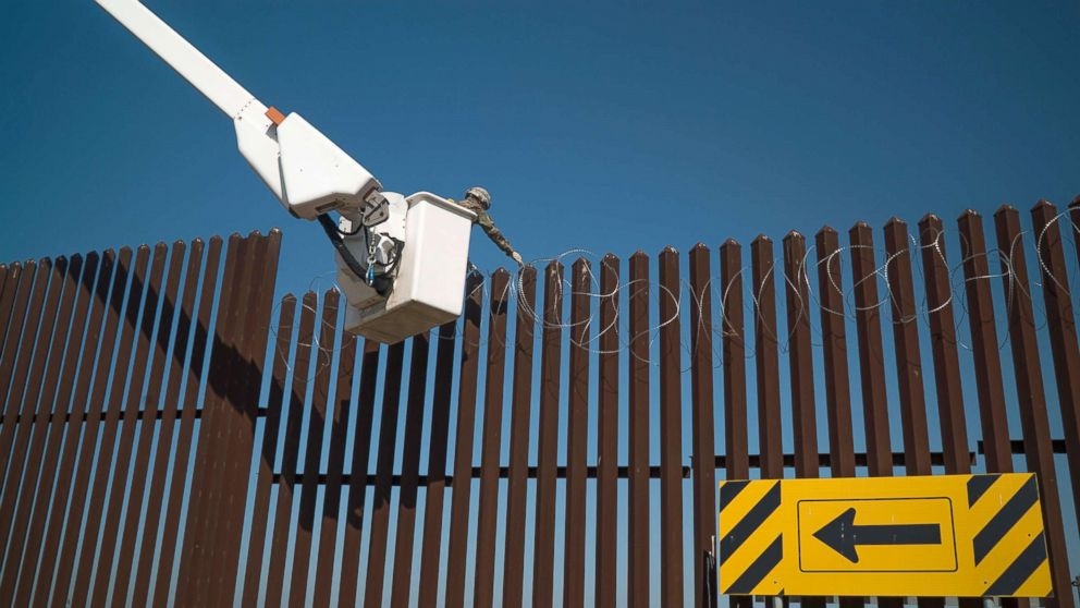 541st Sapper Company Soldiers use a cherry picker to install concertina wire along the top of the border fence in Donna, Texas, Dec. 1, 2018.
