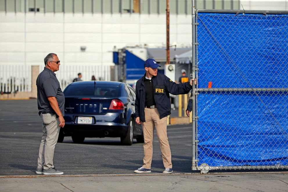 PHOTO: Federal agents stand in a downtown Los Angeles parking lot after predawn raids in the L.A. area, Aug. 22, 2019.
