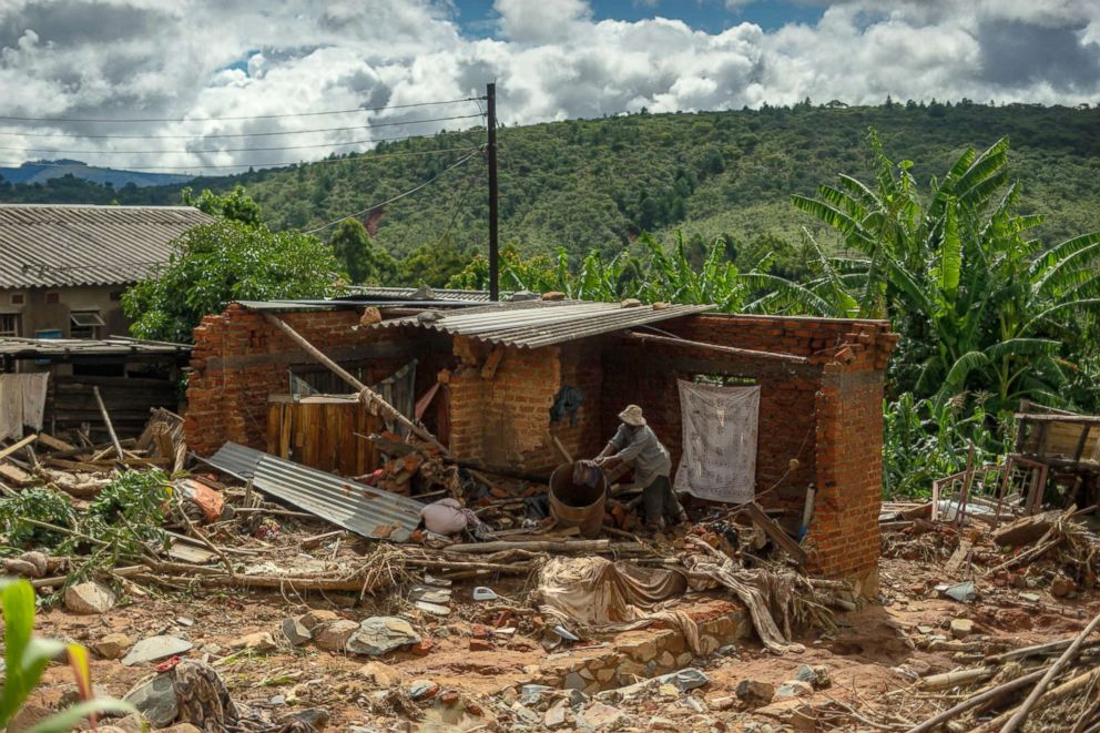 PHOTO: A man cleans up a destroyed house, March 19, 2019, in Chimanimani, Zimbabwe, as a hundred houses were damaged by the Cyclone Idai.