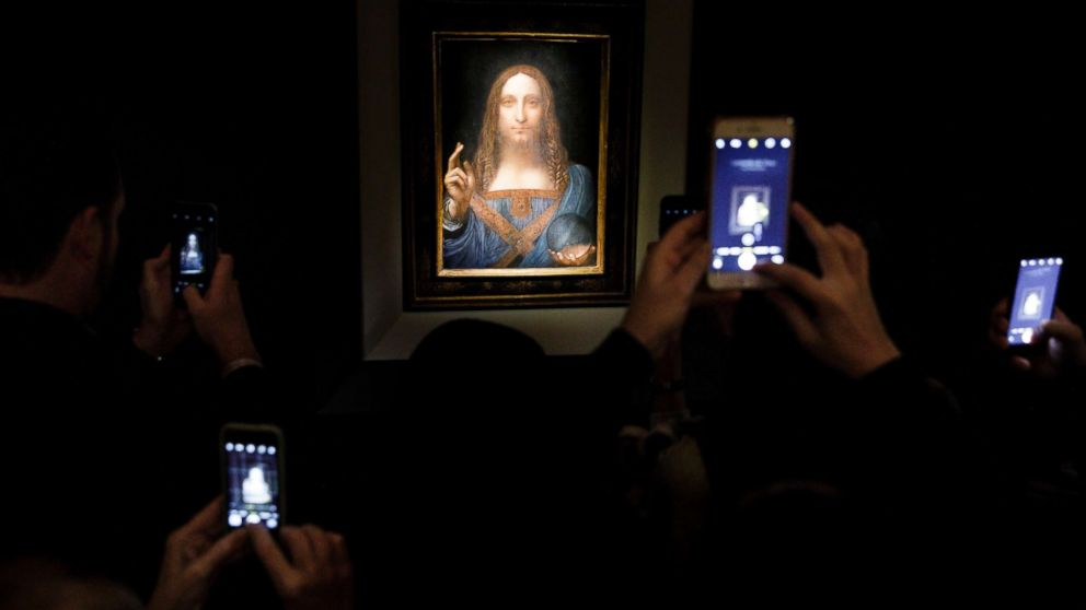 People take pictures of the painting 'Salvator Mundi' by Leonardo da Vinci (circa 1500) during a public preview before an auctioning of the painting tonight at Christie's auction house in New York, Nov. 15, 2017. The painting is reportedly one of only twenty paintings by Da Vinci and is expected to sell for at least 100 million USD.