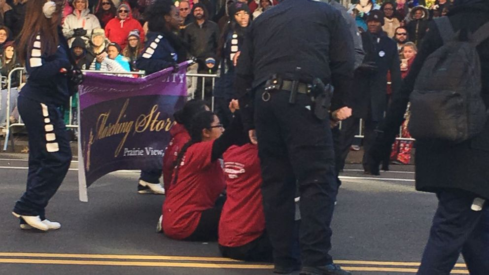 The protesters sat in the middle of Central Park West at 70th Street and momentarily delayed the parade before they were carried off by NYPD police officers.