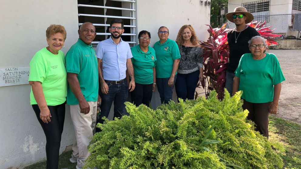 Members of the Social and Cultural Development Committee of Daguao stand alongside a member of the Resilient Power Puerto Rico team.