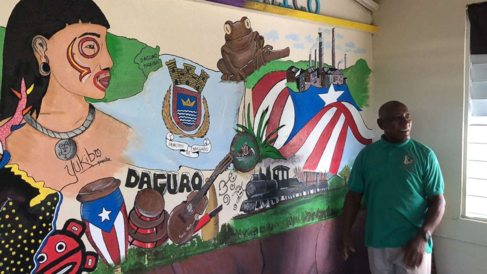 Community leader Angel Colon poses next a mural dedicated to the town of Daguao.