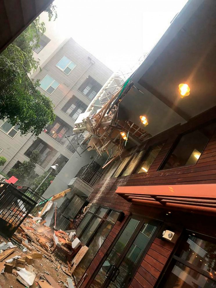 PHOTO: This photo taken and provided by Michael Santana shows the damage after a construction crane toppled on an apartment building as it was buffeted by high winds during a storm in Dallas, Texas, Sunday, June 9, 2019.