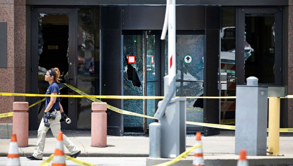 PHOTO: An FBI agent walks past the bullet riddled glass doors of the Earle Cabell Federal Building on June 17, 2019, in Dallas.