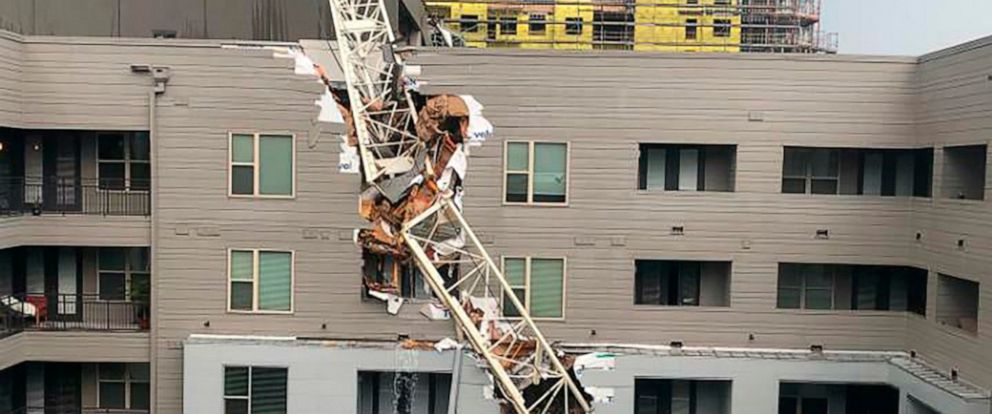 PHOTO: This photo taken and provided by Michael Santana shows a construction crane toppling on an apartment building as it was buffeted by high winds during a storm in Dallas, Texas, Sunday, June 9, 2019.