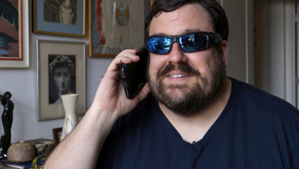 PHOTO: Dan Bell demonstrates how he uses undercover glasses to film in malls.