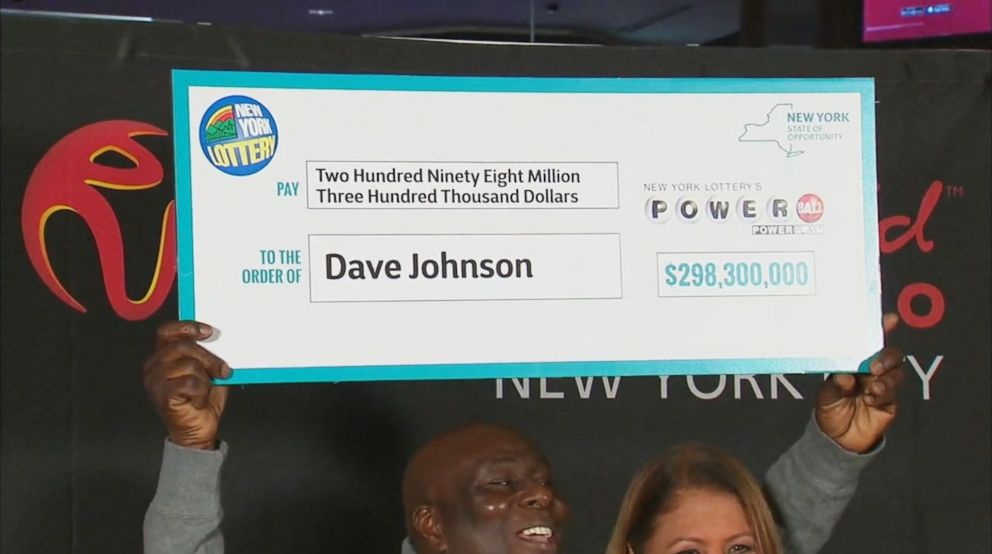 David Johnson, 56, of East New York, accepted his winnings from Yolanda Vega of the New York Lottery Friday at Resorts World Casino in Queens, Jan. 25, 2019.