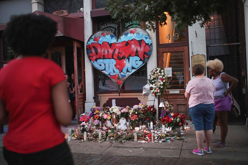 PHOTO: People congregate around a memorial to those killed in Sunday mornings mass shooting on Aug. 6, 2019 in Dayton, Ohio.