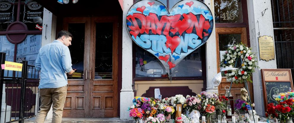 PHOTO: A pedestrian passes a makeshift memorial for the slain and injured victims of a mass shooting that occurred in the Oregon District early Sunday morning, Wednesday, Aug. 7, 2019, in Dayton, Ohio.