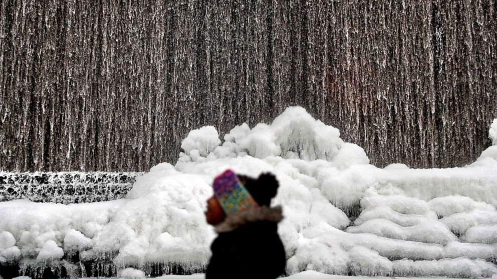 Alora Freeman, 8, watches as ice builds along a downtown water fountain in Atlanta, Jan. 3, 2018.