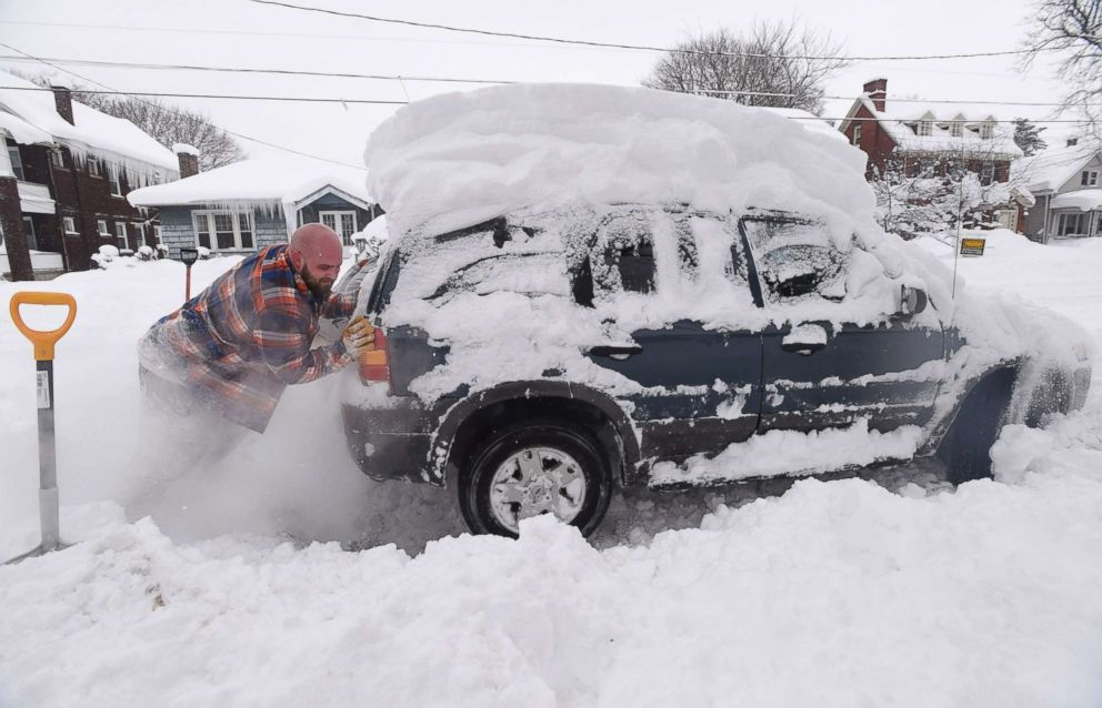 PHOTO: Kevin Deiner of Erie, Pa., pushes his Ford Escape out of the deep snow on West Sixth Street, Dec. 30, 2017.