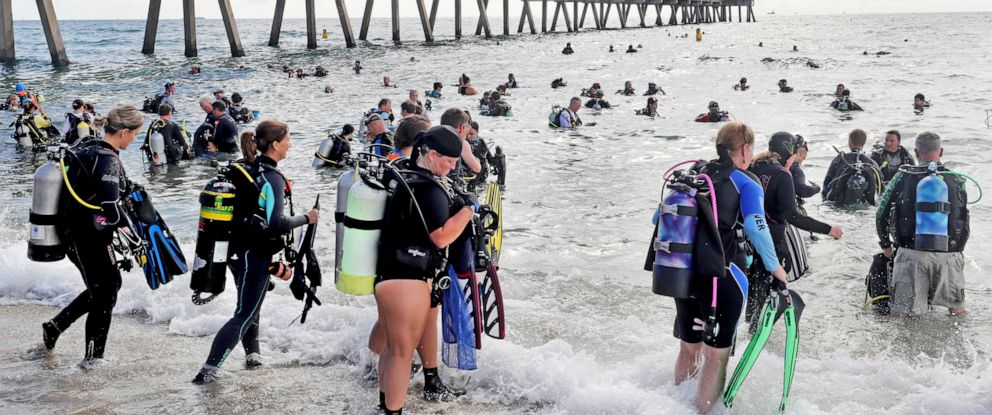 PHOTO: Divers enter the water in an attempt to break the world record for the largest underwater cleanup at the Deerfield Beach International Fishing Pier in Deerfield Beach, Fla., Saturday, June 15, 2019.