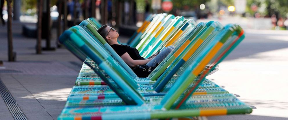 PHOTO: A woman sits in a bank of lounge chairs outside the Denver Art Museum to take advantage of the warm weather as temperatures climbed into the 70s, Oct. 7, 2019, in Denver, before temperatures drop and snow moves in later this week.