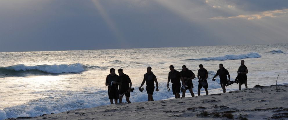 PHOTO: Members of SEAL Team 18 swim into the ocean to release the ashes of fellow SEALs who have died within the last year during a ceremony at Fort Pierce Beach, Fla., Nov. 7, 2010.