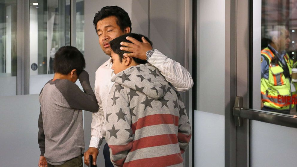 Jesus Lara Lopez, 37, of Willard, Ohio, comforts his sons before he is deported back to Mexico, July 18, at Cleveland Hopkins International Airport.