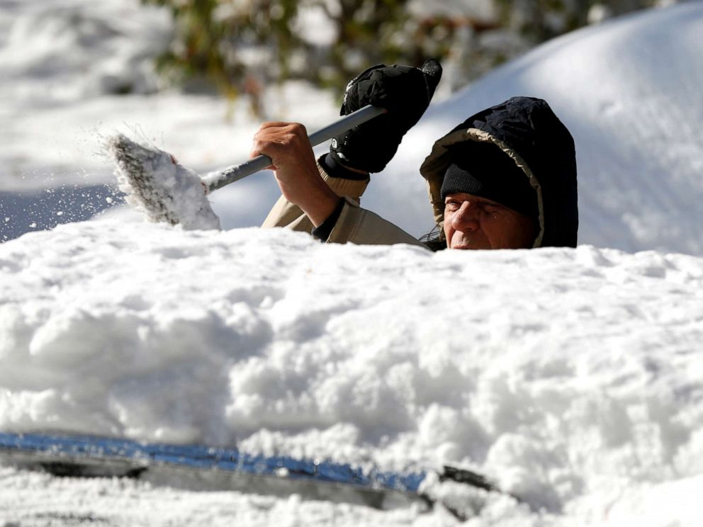 PHOTO: A man cleans the snow from the top of his vehicle in Detroit, Michigan, Nov. 12, 2019.