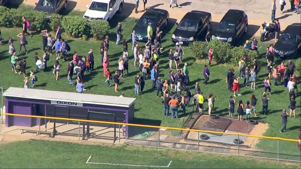People gather a short distance from Dixon High School in Dixon, Ill., after a police officer confronted and injured an armed man at the school, May 16, 2018.