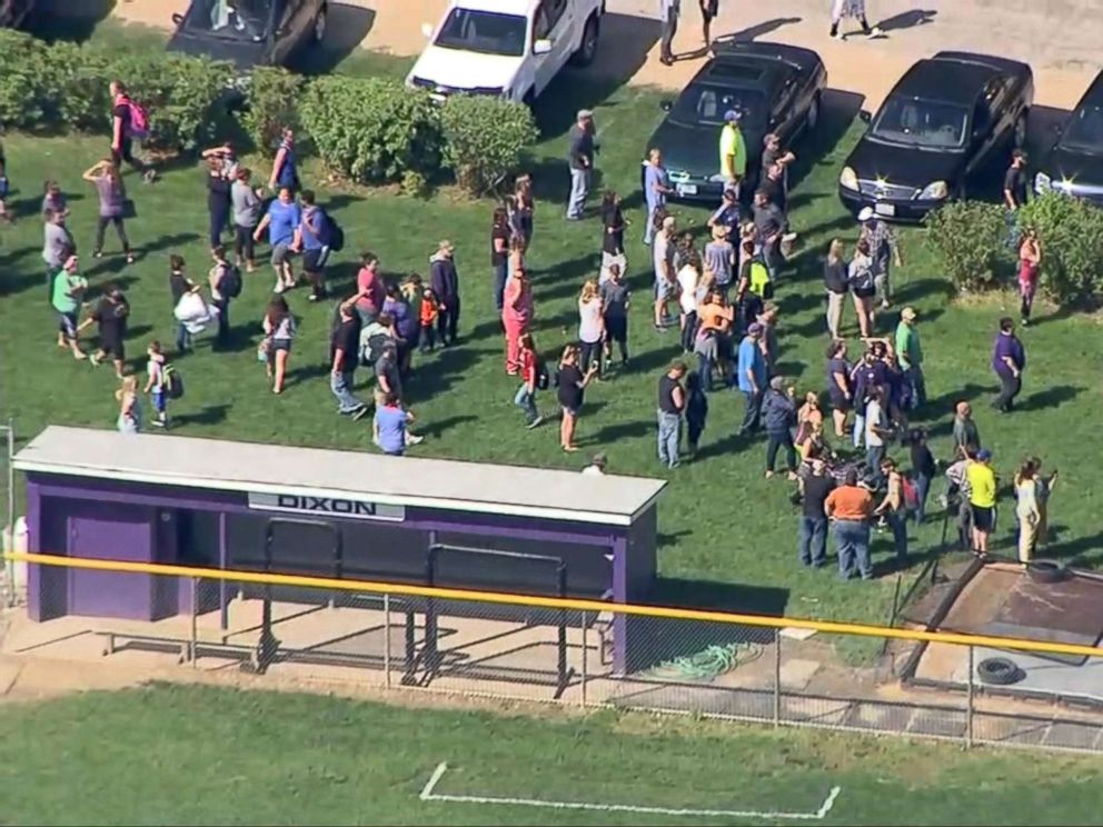 PHOTO: People gather a short distance from Dixon High School in Dixon, Ill., after a police officer confronted and injured an armed man at the school, May 16, 2018.