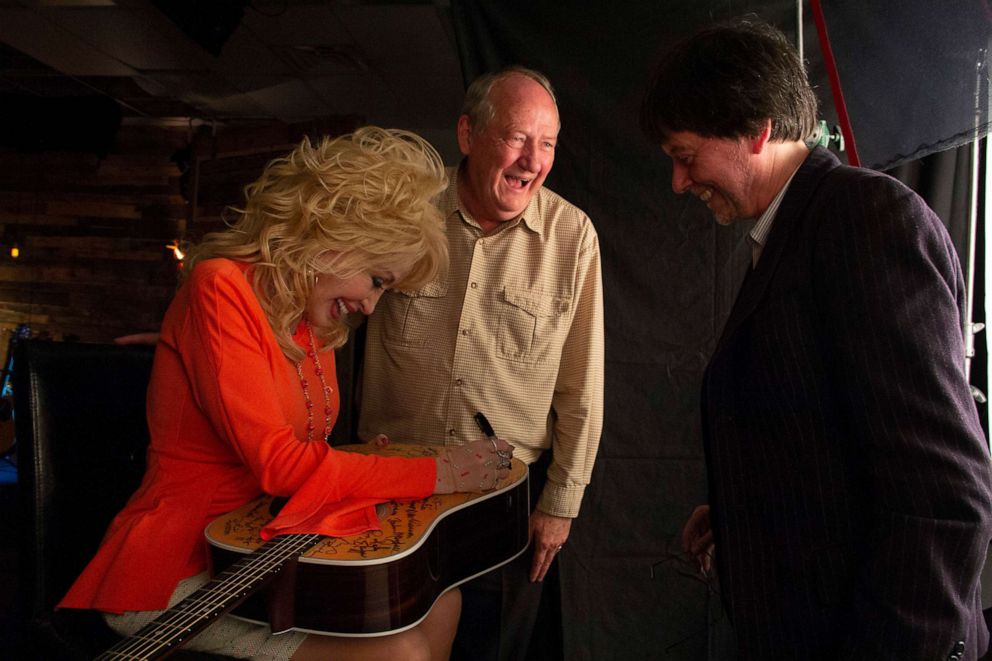 PHOTO: Dolly Parton signs a guitar with Country Music writer Dayton Duncan and director Ken Burns.