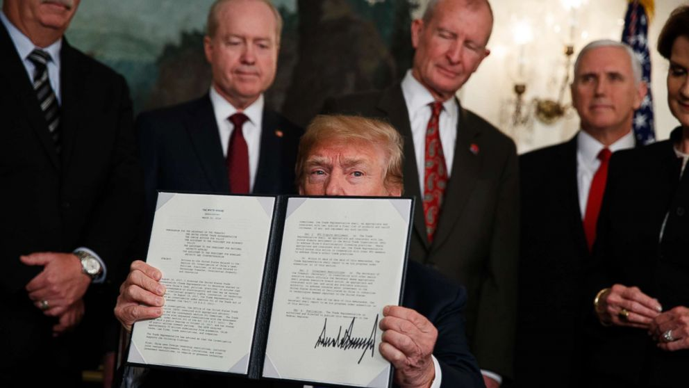 President Donald Trump displays signs a presidential memorandum imposing tariffs and investment restrictions on China in the Diplomatic Reception Room of the White House, March 22, 2018, in Washington.
