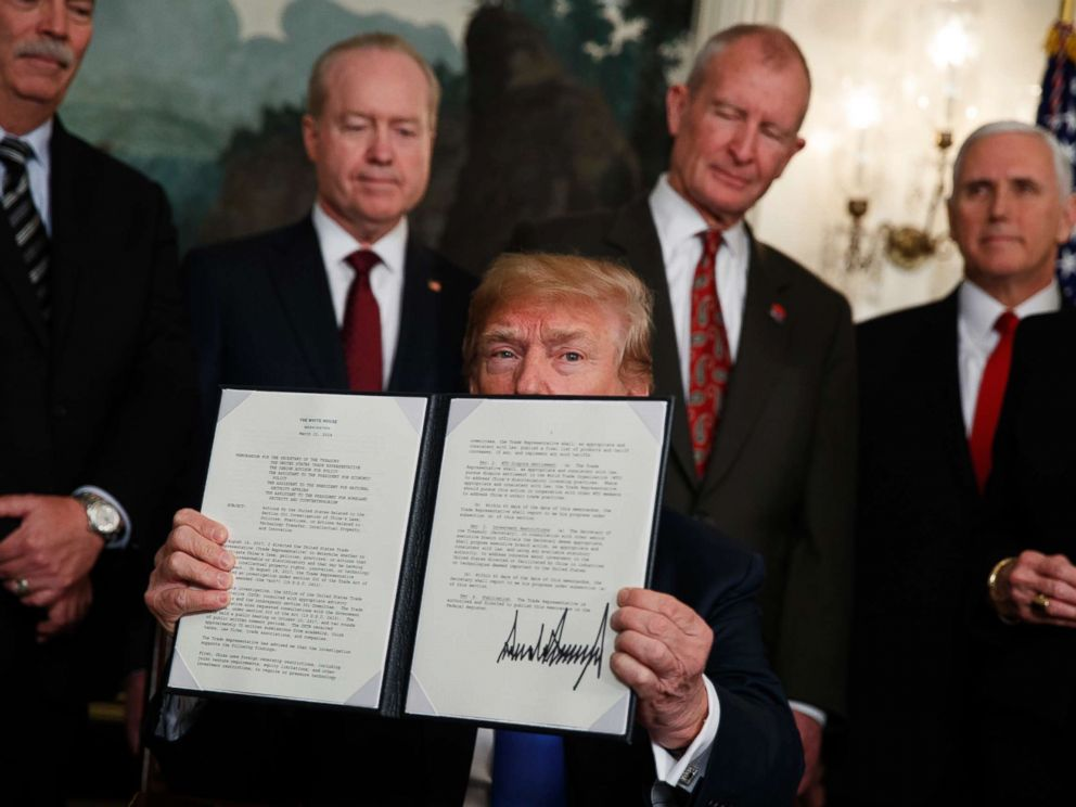 PHOTO: President Donald Trump displays signs a presidential memorandum imposing tariffs and investment restrictions on China in the Diplomatic Reception Room of the White House, March 22, 2018, in Washington.