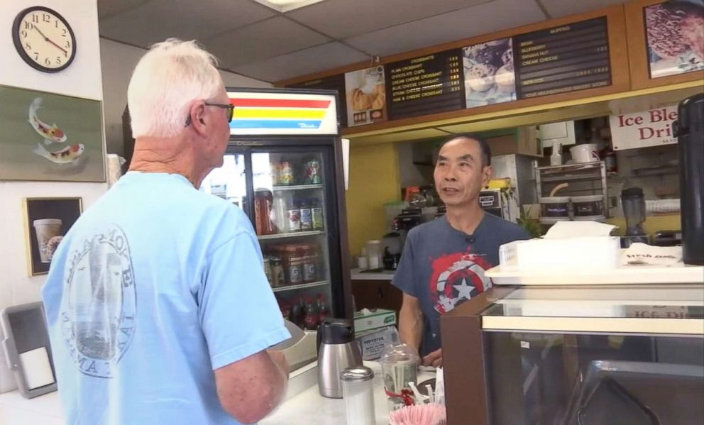 PHOTO: Donut shop owner John Chhan helps one of his customers in Seal Beach, Calif. When his wife, Stalla, fell ill, customers bought up his daily supply so he could close shop and head home to take care of her.