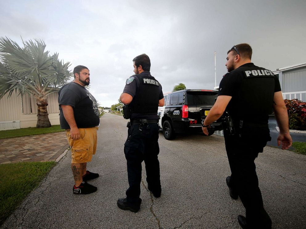 PHOTO: Vero Beach police officers talk to resident Todd Dufresne, left, as they notify residents of a trailer park community of a mandatory evacuation, in preparation for Hurricane Dorian, in Vero Beach, Fla., Sept. 2, 2019.