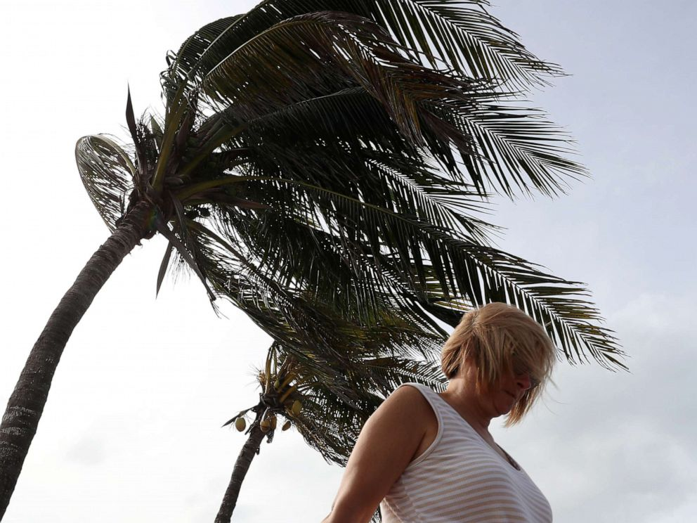 PHOTO: A woman walks by palm trees whipped by winds from Hurricane Dorian, Sept. 2, 2019, in Vero Beach, Fla.