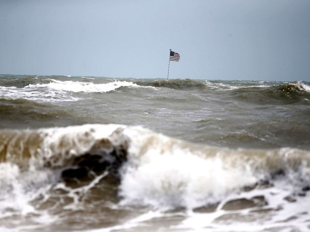 PHOTO: Waves crash in front of an American flag that is planted on a jetty during a high surf from the Atlantic Ocean, in advance of the potential arrival of Hurricane Dorian, in Vero Beach, Fla., Sept. 2, 2019.