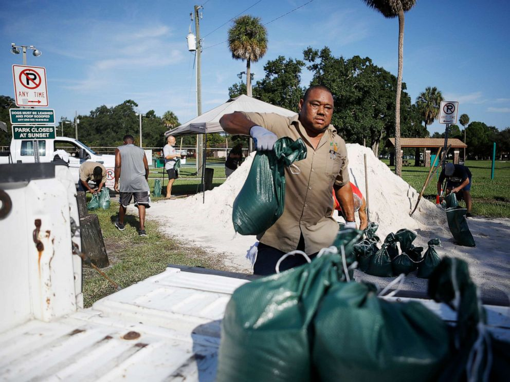 PHOTO: City of Tampa Parks & Recreation employee Rod McKinney helps Horace Whittington 61, of Tampa load sandbags in his truck for his mother 91-year-old mother in preparation for Hurricane Dorian at MacFarlane Park in Tampa, Fla., Aug. 29, 2019.
