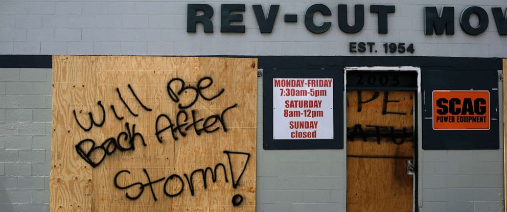 """PHOTO: A boarded up business with """"Will be back after storm"""" painted on it is seen ahead of the arrival of Hurricane Dorian in Cocoa, Fla., Sept. 1, 2019."""