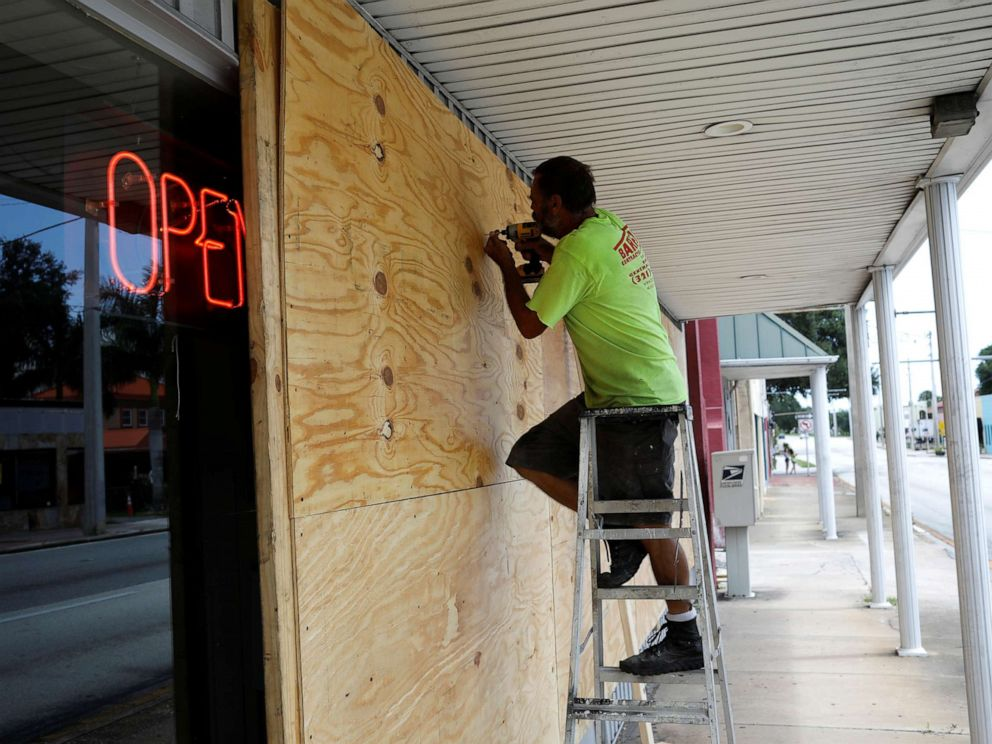 PHOTO: A man boards up a business ahead of the arrival of Hurricane Dorian in Cocoa, Fla., Sept. 1, 2019.