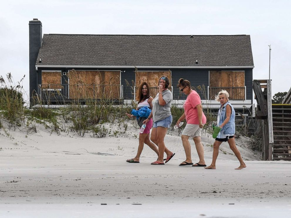 PHOTO: Women walk in front of a boarded up house on the beach in North Litchfield, S.C., Sept. 4, 2019.