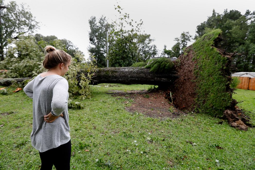 PHOTO: Kelsey Myers looks at an overturned tree in her front yard in Summerville, S.C., after Hurricane Dorian passed by, Sept. 5, 2019, in Summerville, S.C.