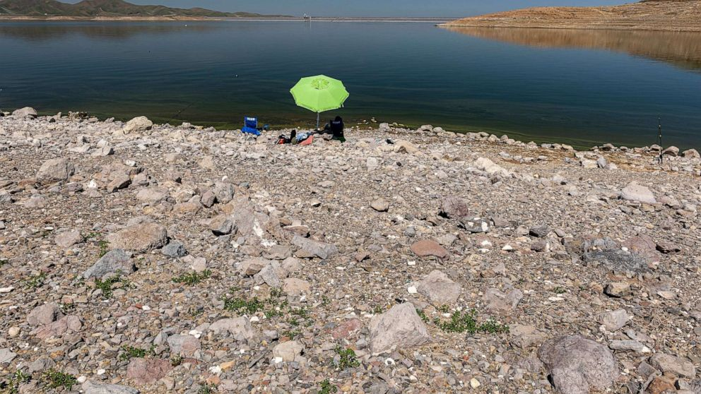 PHOTO: People sit on a dried lake bed at the San Luis Reservoir in Merced County, Calif., April 6, 2021.