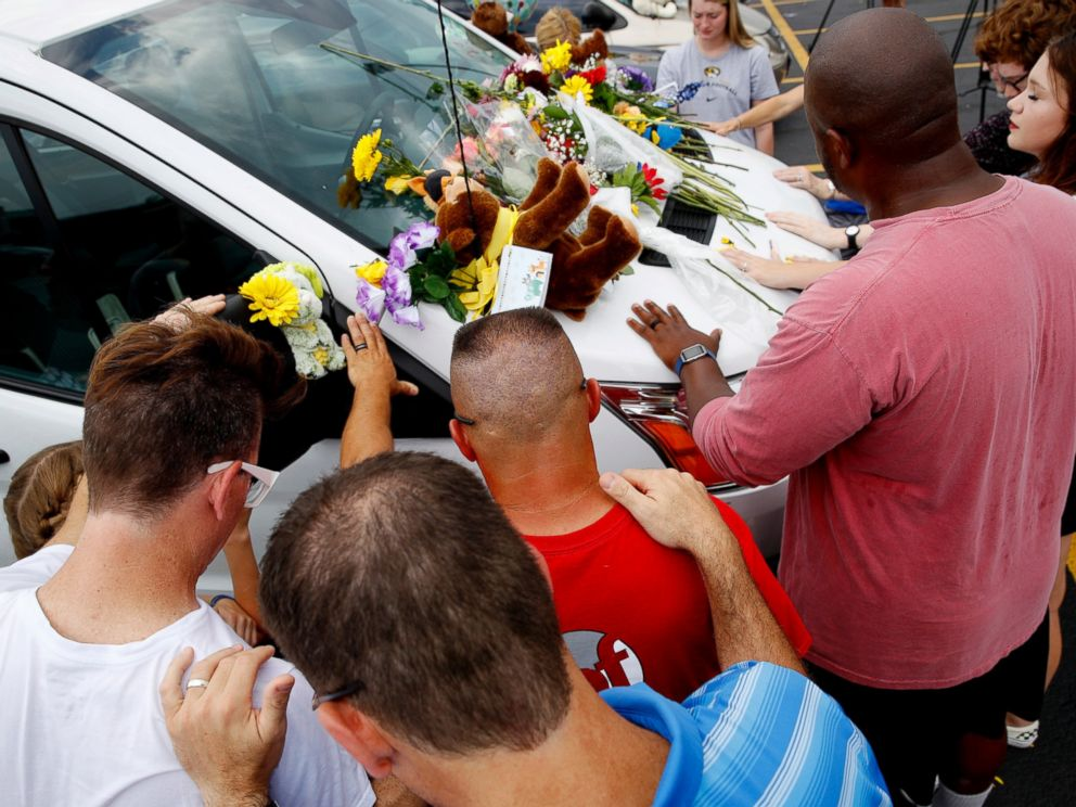 People pray around a van believed to belong to victims of a duck boat accident in the parking lot of the business running the boat tours Friday, July 20, 2018 in Branson, Mo.