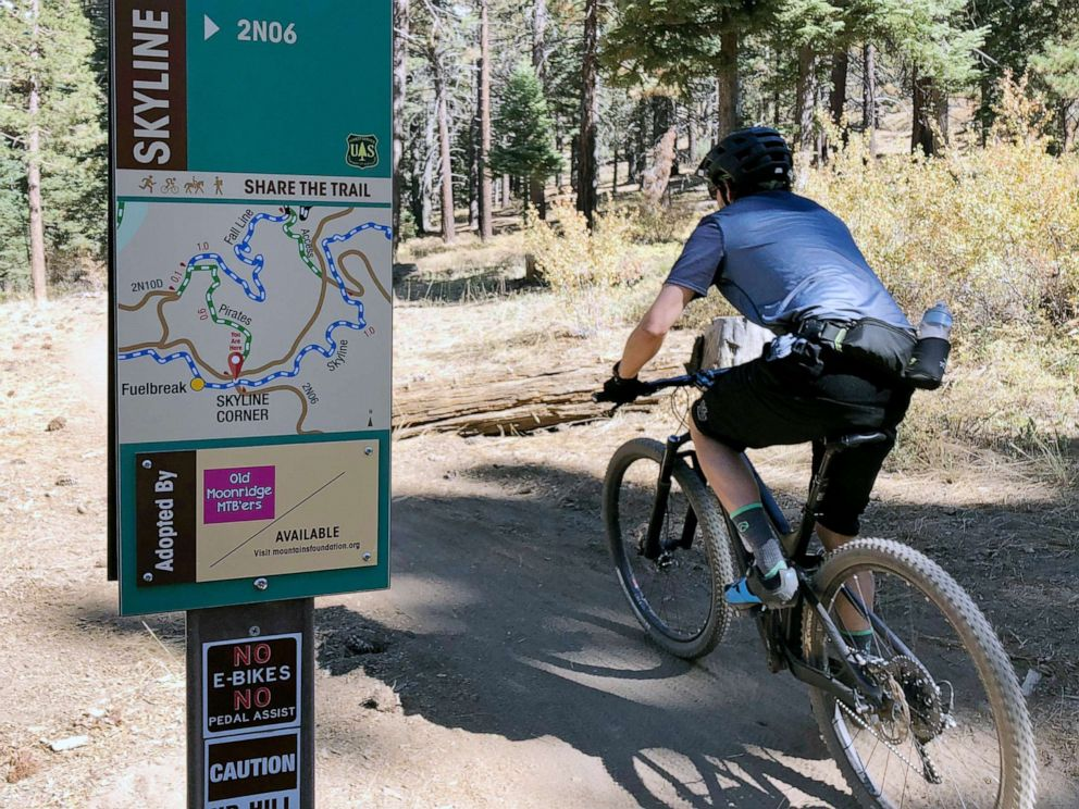 PHOTO: In this photo taken Sept. 23, 2018, a mountain biker pedals past a No E-bikes sign in the San Bernardino National Forest near Big Bear Lake, Calif.