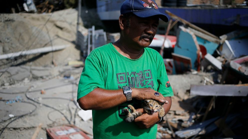 Sa'adon Lawira holds his grandson's cat whose miauw helped him finding his body which was buried under the rubble of the family's house in Balaroa neighborhood in Palu, Central Sulawesi, Indonesia Indonesia, Tuesday, Oct. 2, 2018.