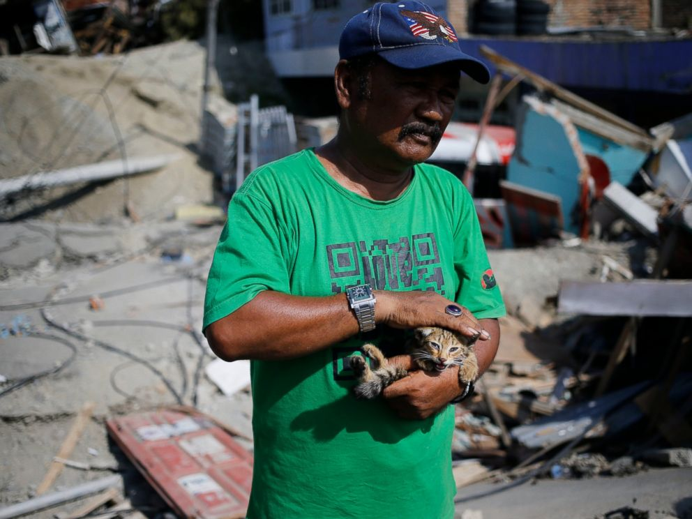 PHOTO: Saadon Lawira holds his grandsons cat whose miauw helped him finding his body which was buried under the rubble of the familys house in Balaroa neighborhood in Palu, Central Sulawesi, Indonesia Indonesia, Tuesday, Oct. 2, 2018.