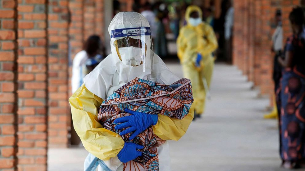 A health care worker carries a baby suspected of being infected with Ebola virus in a hospital in Oicha, North Kivu Province of Democratic Republic of Congo, Dec. 6, 2018.