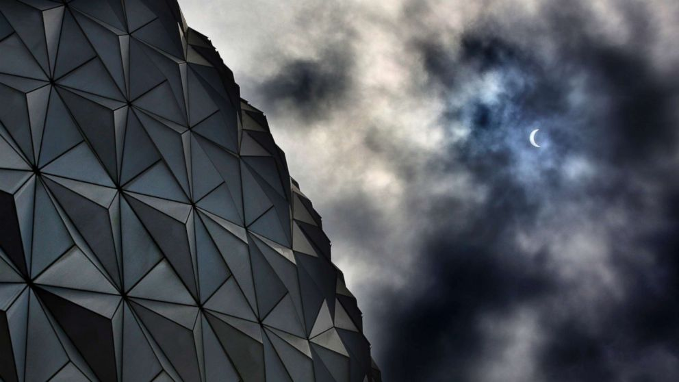 Rain clouds obscure the solar eclipse tracking over Spaceship Earth at Epcot at Walt Disney World in Lake Buena Vista, Florida, Aug. 21, 2017.