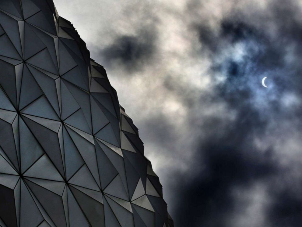 PHOTO: Rain clouds obscure the solar eclipse tracking over Spaceship Earth at Epcot at Walt Disney World in Lake Buena Vista, Florida, Aug. 21, 2017.