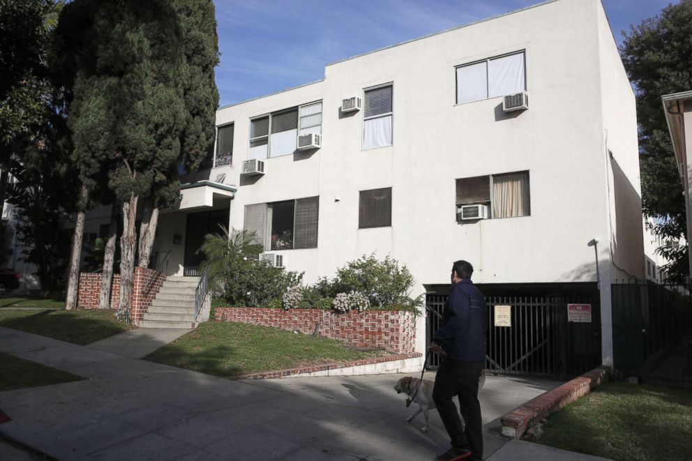 PHOTO: A man walks his dog past an apartment building, Jan. 8, 2019, where an unidentified man died in the apartment of Democratic Party donor Ed Buck, in West Hollywood, Calif.