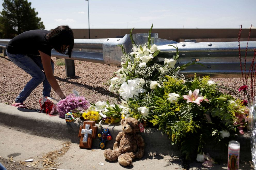 PHOTO: A woman places flowers at the site of a mass shooting at a Walmart in El Paso, Texas, Aug. 4, 2019.